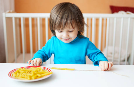 A young boy sits at a table wearing a blue shirt and stretching out a string with macaroni noodles on it. A plate of dried macaroni sits beside him.